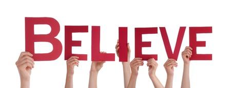 Muchas Manos que sostienen la palabra creer, aislado Foto de archivo