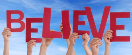 believe: Many Hands Holding the Red Word Believe in Front of a blue Sky Stock Photo