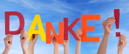 agradecimiento: Muchas Manos que sostienen la Danke palabra alemana que significa gracias en frente del cielo