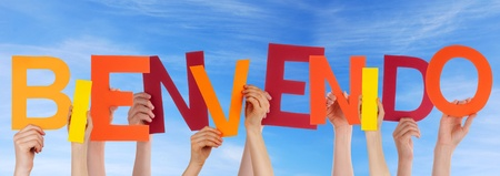 bienvenido: Many Hands Holding the Colorful Spanish Word Bienvenido in the Sky Which Means Welcome