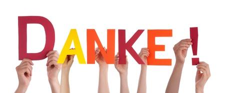 agradecimiento: Muchas personas Holding Danke la palabra alemana que significa Gracias, Aislado