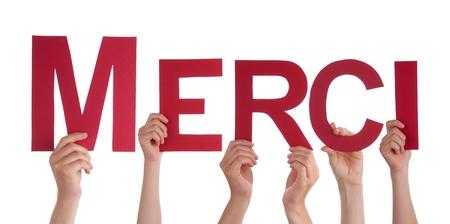 agradecimiento: Muchas Manos que sostienen la palabra francesa Merci, lo que significa Gracias, Aislado