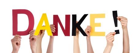 agradecimiento: Personas Holding del Danke palabra alemana que significa Gracias en los colores de Alemania, Aislado Foto de archivo