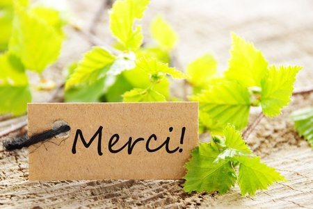 A Label With the French Word Merci Which Means Thanks photo