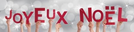 joyeux: Many Hands Holding the French Words Joyeux Noel on a Silver Background Stock Photo