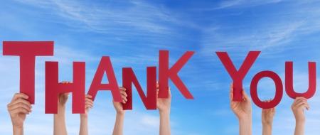 merci: Beaucoup de gens tenant le mot de remerciements dans le ciel Banque d'images