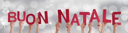 buon: Many People Holding the Italian Words Buon Natale Which Means Merry Christmas on a Silver Background