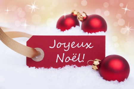 A Red Label with the French Words Joyeux Noel Which Means Merry Christmas on It photo