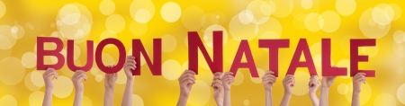 buon: Many Hands Holding the Italian Words Buon Natale Which Means Merry Christmas on a Golden  Stock Photo