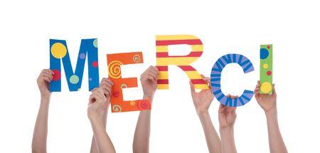 agradecimiento: Muchas Manos que sostienen la palabra francesa colorida Merci, lo que significa Gracias, Aislado