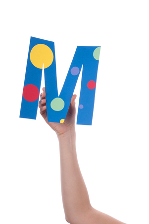 illiterate: A Hand Holding a Colorful M, Isolated Stock Photo