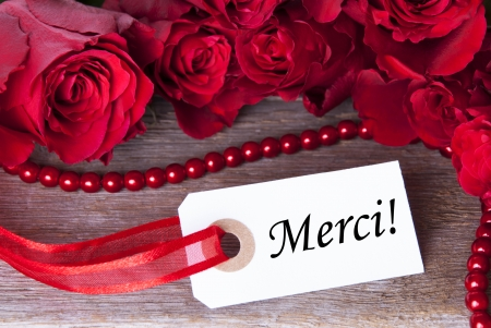A Background with Red Roses and a White Ticket with the French Word Merci on it Which Means Thanks photo
