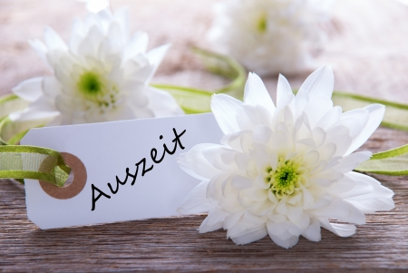 auszeit: White Flower Background with a Label with the German Word Auszeit on it which means Downtime Stock Photo