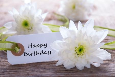 flores de cumpleaños: Un Fondo de flor blanca con una etiqueta con el feliz cumpleaños en él Foto de archivo