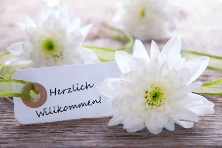 White Label with white flowers and the German Words Herzlich Willkommen which means Welcome photo
