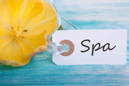 healthfulness: Label with Spa on turquoise Background with Yellow Tulip Blossom