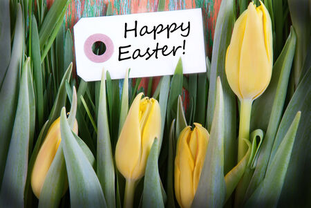 Easter Background with a Label with Easter Greetings and Yellow Tulips photo