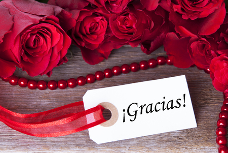 A Background with Red Roses and the Spanish Word Gracias Which Means Thanks photo