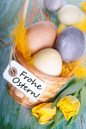 frohe: Eggs in a Basket with a Label with the German Words Frohe Ostern which means Hapy Easter