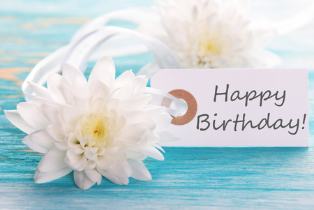 birthday backdrop: Label with Happy Birthday on wooden turquiose with white Flowers Stock Photo