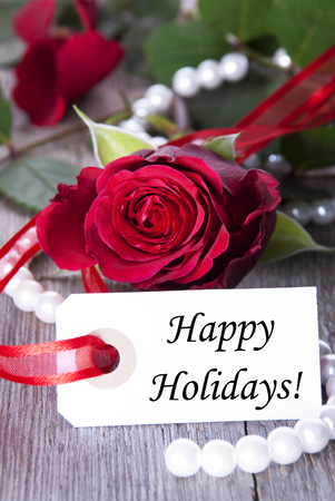 Label with Happy Holidays and a rose as festive Background photo