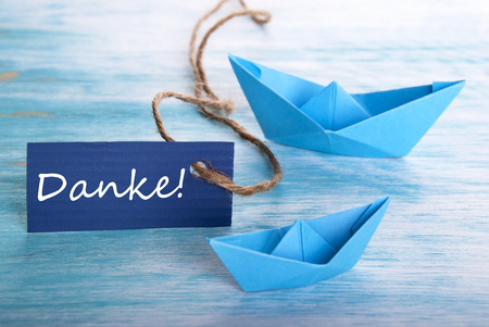 The German Word Danke Which Means Thanks on a Label with a Boat Background photo