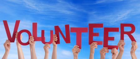 Handen met het woord vrijwilliger in the Sky Stockfoto