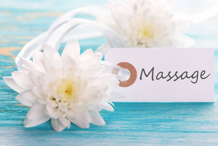 healthfulness: Label with Massage on turquiose wooden Background with white Flowers