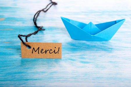 The French Word Merci Which Means Thanks on a Label with a Boat in the Background photo