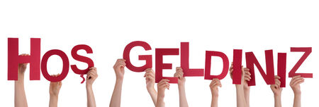 welcom: Many Hands Holding the Turkish Words Hos Geldiniz which means Welcome, Isolated Stock Photo