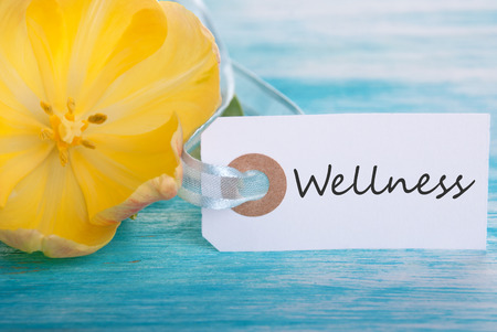 healthfulness: Tag with Wellness on turquiose Boars with Yellow Tulip Blossom