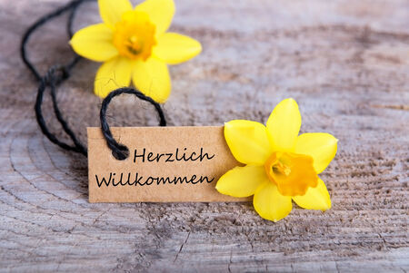 Label with Narcissus and the German Words Herzlich Willkommen, which means, Welcome photo