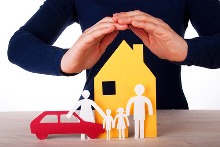 home insurance: Two Hands are Protecting a Family infront of its House with their Car, Isolated