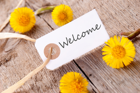 White Banner with the Word Welcome with many yellow Flowers photo