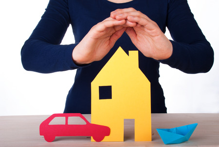 Womans Hands Guarding a House, a Car and a Boat, Isolated photo