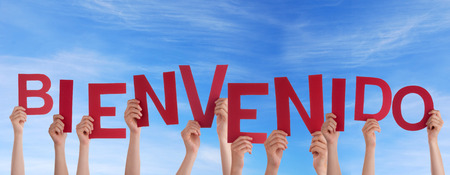 bienvenido: Many Hands Holding the Spanish Word Bienvenido in the Sky which means Welcome