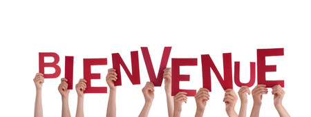 Many People Holding the French Word Bienvenue which means Welcome, Isolated photo