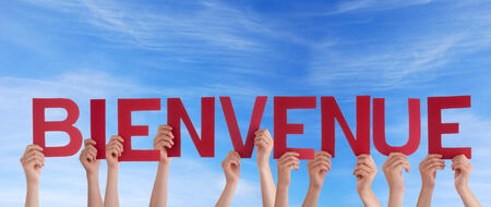 bienvenido: Many Hands Holding the French Word Bienvenue in the Sky which means Welcome