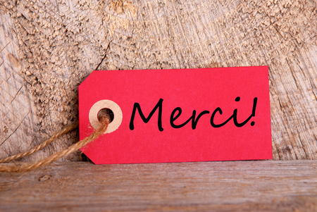 A Red Tag on Wood with the French Word Merci which means Thanks photo