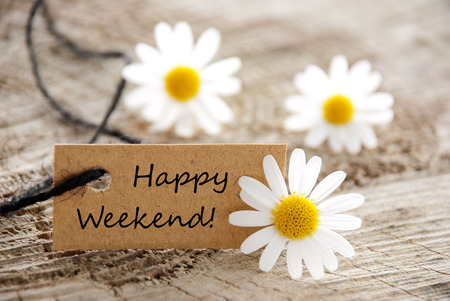 weekend: A Natural Looking Label with Happy Weekend on it and White Flowers in the Background Stock Photo