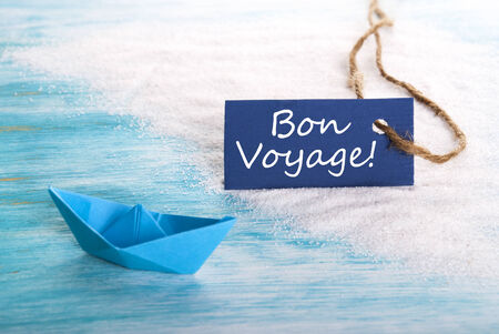 A Blue Label with Bon Voyage which means Safe Trip at the Beach with a Boat photo