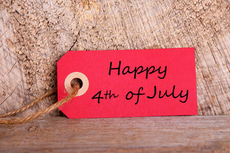 A Red Tag with the Words Happy 4th of July, on Wood photo