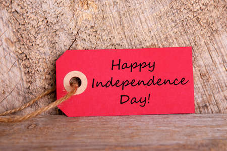 A Red Tag with the Words Happy Independence Day, on Wood photo