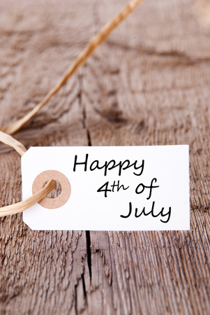 A White Banner on Wood with the Words Happy 4th Of July photo