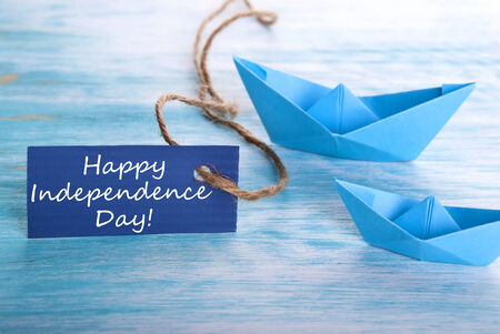 A Blue Tag with Happy Independence Day and Boats in the Background photo