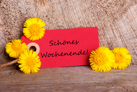 wochenende: A Red Banner with the German Words Schoenes Wochenende which means Happy Weekend and with Yellow Flowers