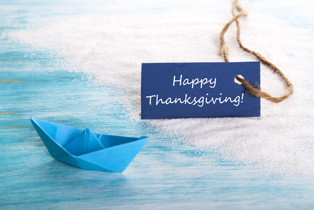 A Blue Label with Happy Thanksgiving on it at a Beach with a Boat Stock Photo