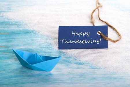 Ein Blue Label mit Happy Thanksgiving darauf an einem Strand mit einem Boot