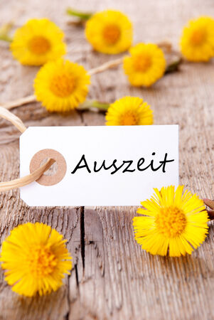auszeit: White Banner with the German Word Auszeit which means Downtime and many yellow Flowers Stock Photo