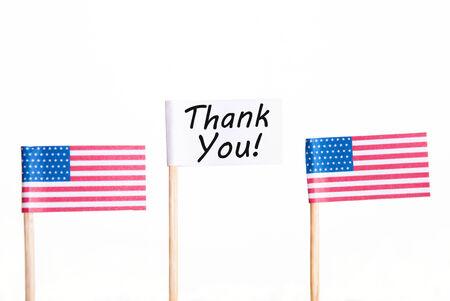 drapeaux am�ricain: Drapeau blanc avec Merci � c�t� de deux drapeaux am�ricains, isol� Banque d'images